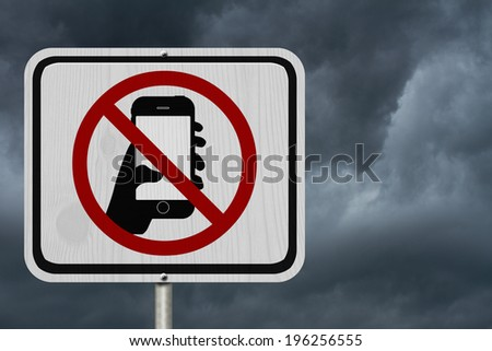 No Texting and Driving Sign, White Information sign with symbol of a hand and texting with stormy sky background - stock photo