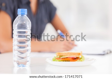 No time for break. Cropped image of woman writing something in her note pad while sandwich and a bottle of water laying on foreground - stock photo