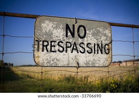 No trespassing sign against backdrop of farmland being encroached by housing development. Urban sprawl concept. - stock photo