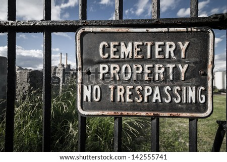 No trespassing sign on iron cemetary fence - stock photo