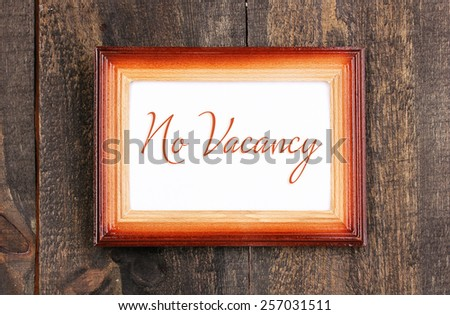 No Vacancy text in frame on wooden background - stock photo
