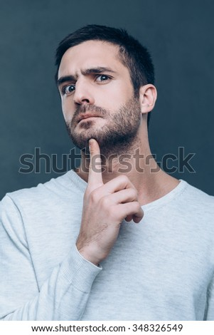 No way! Frustrated young man touching his chin with finger and looking at camera while standing against grey background - stock photo