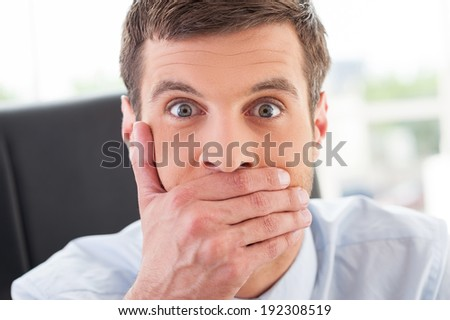 No way! Shocked young man in formal wear covering mouth with hand and looking at camera while sitting at his working place - stock photo