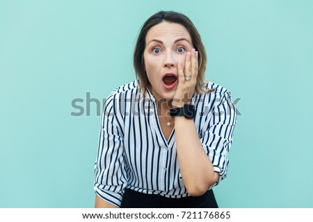 No way! Surprised business woman lady with opened mouth and big eyes. Looking at camera and touching her face. Isolated on blue background, studio shot