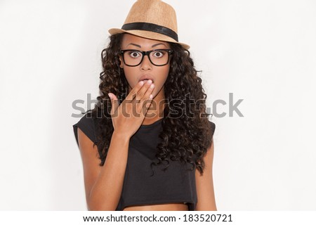 No way! Surprised young African woman in glasses and funky hat covering mouth with hand and looking at camera while standing against white background - stock photo