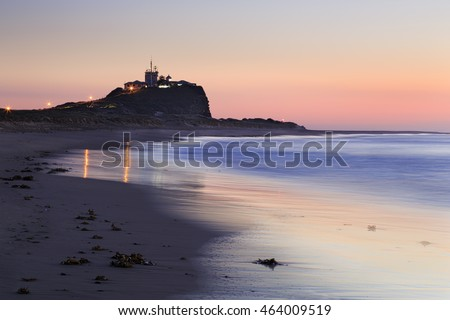 Nobbys head at the end of narrow sandy beach of Newcastle regional town in NSW, Australia. Golden pink rising sun illuminating the old castle and open beach