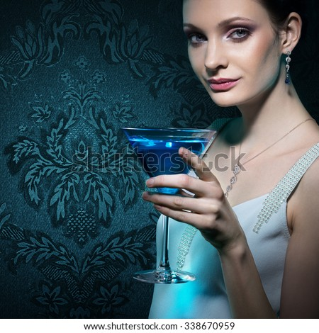 Noble beautiful woman with martini glass on damask wallpaper background - stock photo