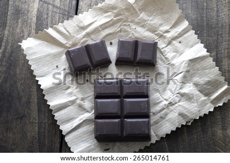 Noble dark chocolate on a wooden table, from above - stock photo