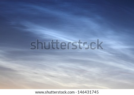 Noctilucent clouds against the sky at twilight. These clouds are part of a phenomenon where the light of the sun is reflected even long after sunset due to their extreme high altitude.