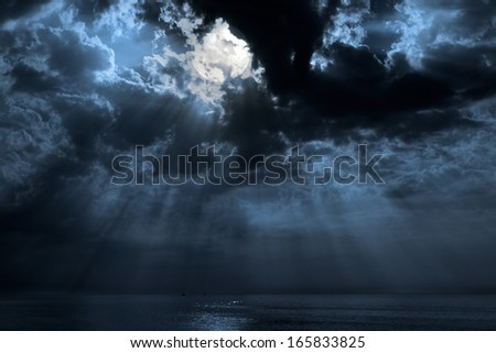 Nocturnal photo composition with moon, clouds, light beams and sea - stock photo