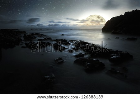 Nocturnal photo composition with moon, clouds, stars, sea and waves - stock photo