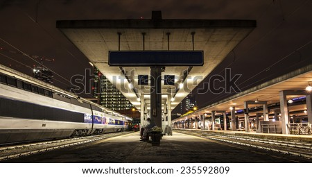 Nocturnal view of a train station. A man looks at his smartphone  - stock photo