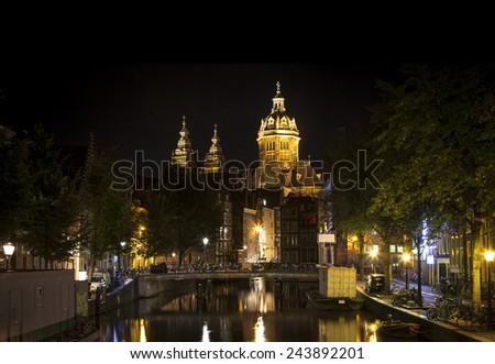 Nocturnal view of Amsterdam: Church of Saint Nicholas and canal in the Red District  - stock photo
