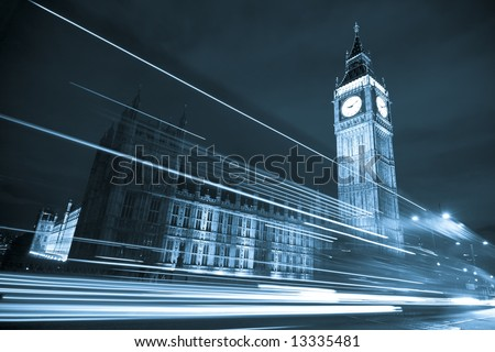 Nocturne scene with Big Ben behind light beams, blue toned. - stock photo