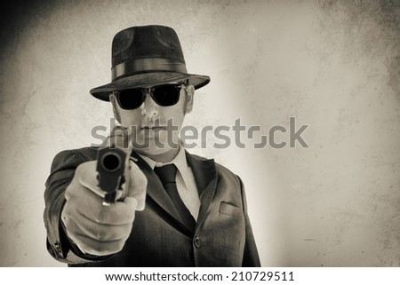 Noir Man Pointing Gun Right Hand. Man in suit, hat and sunglasses pointing a gun at the camera. - stock photo