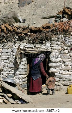 Nomad family near stone hut - stock photo
