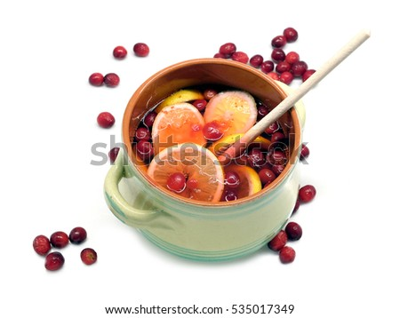 Non-alcoholic drink from cranberries and lemon in big round green pot with wooden spoon inside and scattered berries isolated on white background indoor top view close up