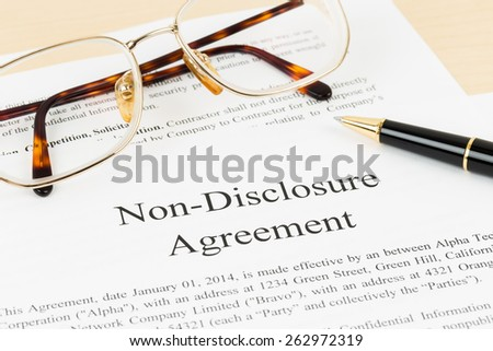 Non disclosure agreement document with pen and glasses; document is mock-up