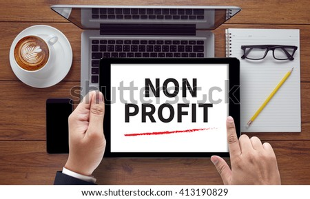 NON PROFIT , on the tablet pc screen held by businessman hands - online, top view - stock photo