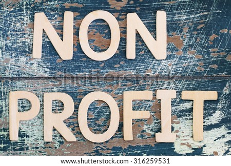Non profit written with wooden letters on rustic surface  - stock photo
