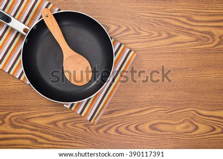 non stick frying pans on wooden background - stock photo