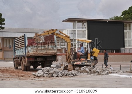 NONG KHAI, THAILAND - August 29, 2015: Tracked Excavator takes the rubble to the truck to clear the area for work  at Mueang Nong Khai Municipality, Thailand  - stock photo