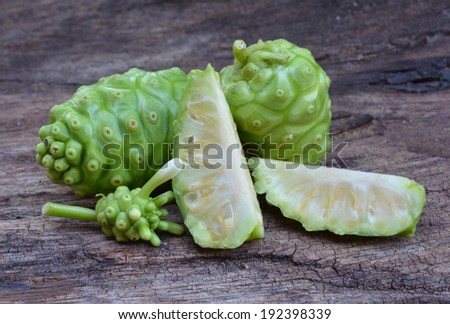 noni fruit on wood - stock photo