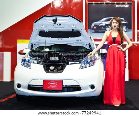 NONTABURI,THAILAND-MAY,15: a Nissan Leaf electric vehicle on display with pretty girl at the Super Car & Import Car Show,May 15,2011 in Nontaburi, Thailand - stock photo