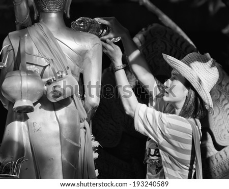 NONTHABURI THAILAND-APRIL13:Un identified woman showering buddha statue in Songkran festival on April 13, 2012 in Nonthaburi,Thailand .  - stock photo
