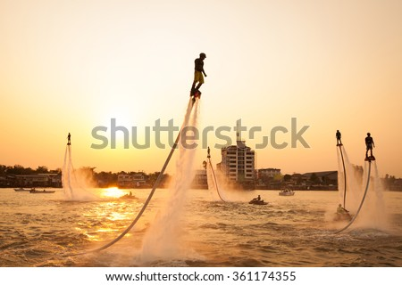 NONTHABURI, THAILAND - March 1, 2015:  Silhouette and vintage color styl  of showing flyboard on Chaophya river during Chinese new year celebrations on March 1, 2015 Nonthaburi, Thailand. - stock photo