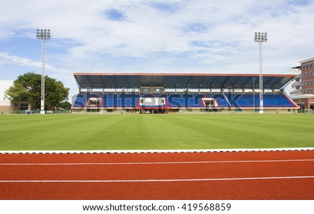 NONTHABURI, THAILAND - SEPTEMBER 27 : Red treadmill, Red running track at the stadium with green grass on blue sky. September 27, 2013 in Nonthaburi, Thailand - stock photo