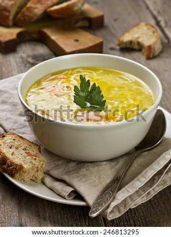 noodle soup in a bowl, slices of bread and spoon on a wooden background
