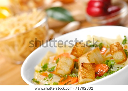 Noodle soup with carrots, croutons and vegetables - stock photo