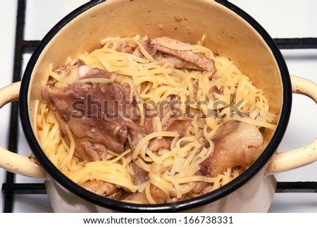 Noodles with chicken meat in pan on gas cooker - stock photo