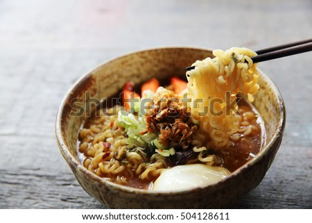 Noodles with egg spicy soup on wood background