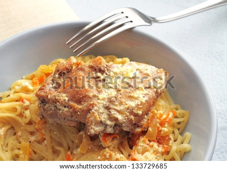 Noodles with rabbit stewed with carrots and onions in sour cream
