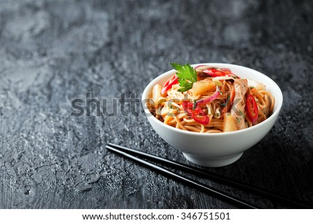 Noodles with vegetables, chicken and pineapple in sweet and sour sauce, selective focus - stock photo