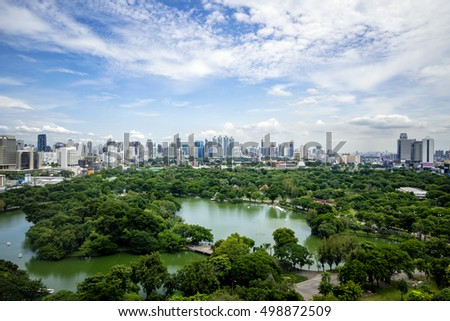 Noon period cityscape at Lumphini Park, Bangkok, Thailand. Lumphini Park (or Lumpini Park) is a park in Bangkok, Thailand. The sky is cloudy.