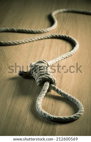 Noose lying on hardwood floor, suicide and punishment concept. - stock photo