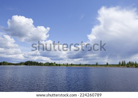 Nordic countryside during summertime. Lake, sky, clouds and farm on a ridge. Bright sunshine.
