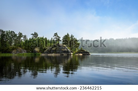 nordic landscape: lake, forest on the rock, fog over the water - stock photo
