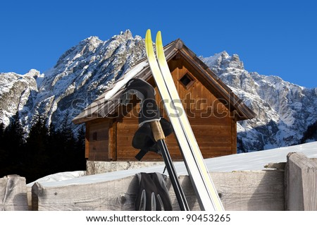 Nordic Skiing in the foreground and Wooden chalet in winter - Alps Italy - stock photo