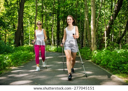 Nordic walking - active people working out in park  - stock photo