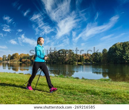 Nordic walking adventure and exercising - young woman hiking with nordic walking poles in park along river - stock photo