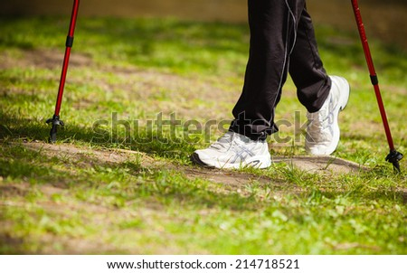 Nordic walking. Closeup of female legs hiking in the park. Active and healthy lifestyle.