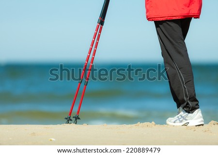 Nordic walking. Closeup of female legs hiking on the beach. Active and healthy lifestyle.
