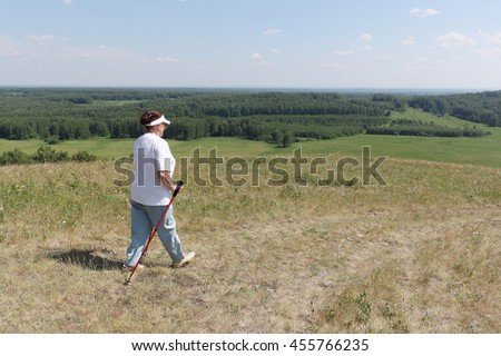 Nordic Walking - elderly woman is hiking  in the summer - stock photo