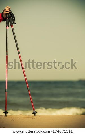 Nordic walking equipment. Closeup of red sticks on the sandy beach. Active and healthy lifestyle. - stock photo