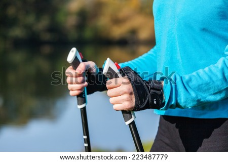 Nordic walking exercise adventure hiking concept - closeup of woman's hand holding nordic walking poles - stock photo