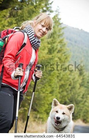 Nordic Walking in Autumn mountains with purebred Akita Inu dog. Hiking concept. - stock photo